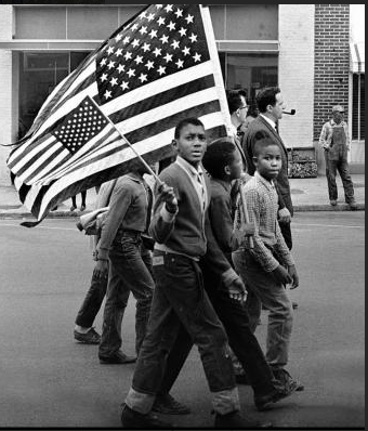 Black boys marching with flags for voting rights
